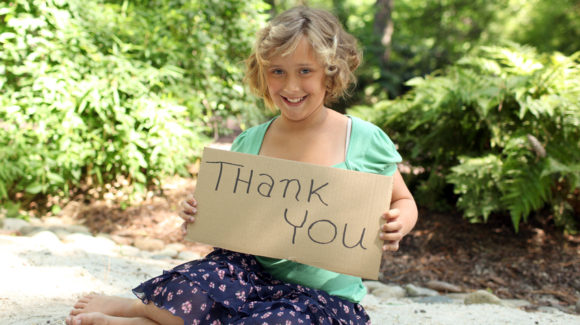 Little girl holding thank you sign