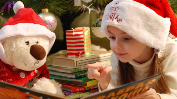 Little girl reads a book by Christmas tree
