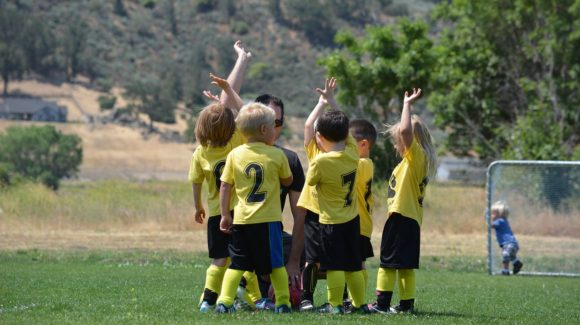 children playing soccer with hands in the air